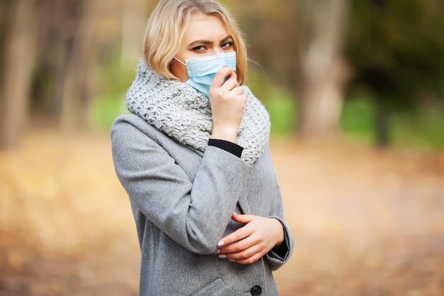Starnuto all'aperto del ritratto della donna perché raffreddore e influenza