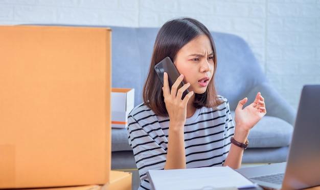 Startup piccola impresa, giovane proprietario di donna asiatica che parla allo smartphone con i clienti sull'ordinazione di prodotti, il venditore prepara la scatola di consegna.