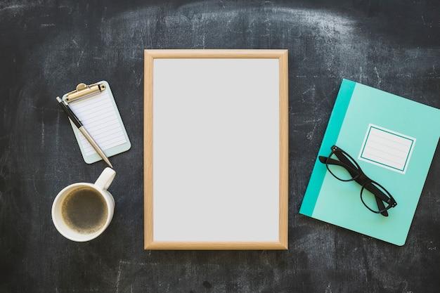 Stationeries; tazza di caffè; taccuino; occhiali e cornice bianca sulla lavagna