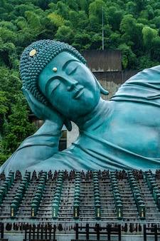 Statua adagiantesi del buddha al tempiale di nanzoin in sasaguri, prefettura di fukuoka, giappone