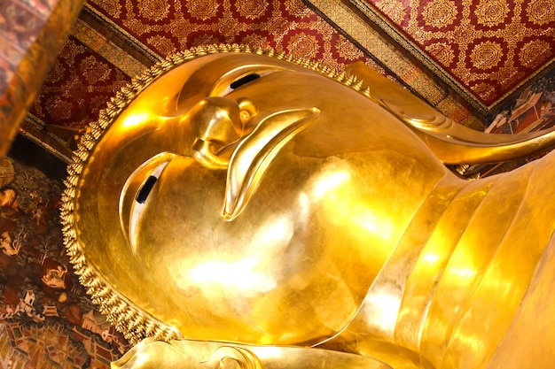 Statua adagiantesi dell'oro del buddha, wat pho, bangkok, tailandia.