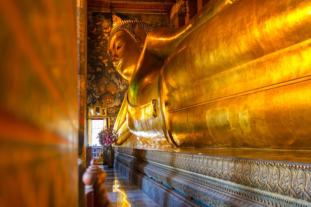 Statua adagiantesi dell'oro del buddha, wat pho, bangkok, tailandia