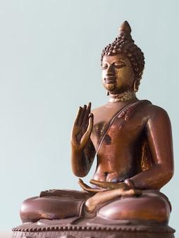 Statua antica del buddha con il percorso di residuo della potatura meccanica. lo sfondo è grigio pervinca