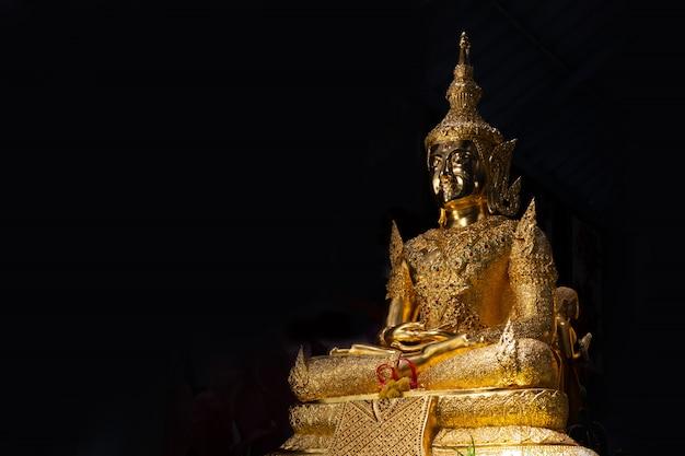 Statua del buddha dell'oro su blackground posteriore