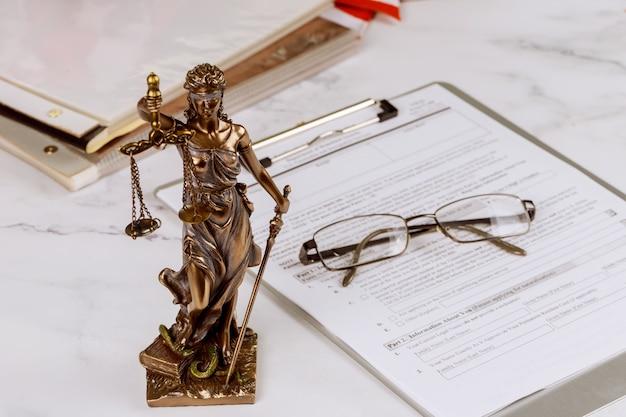Statua della giustizia con il posto di lavoro dell'ufficio per la legislazione dell'avvocato con il martelletto e il documento