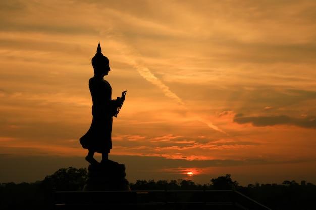 Statua di buddha della siluetta contro il cielo di tramonto