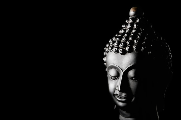 Statua di buddha su sfondo nero. spazio libero per il testo