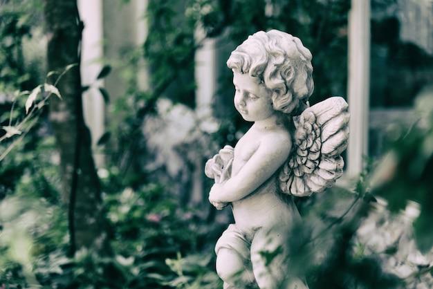Statua di cupido di bellezza di angelo nel giardino d'epoca in estate