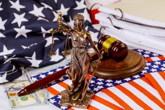 Statua di giustizia dello scrittorio degli avvocati in martelletto della corte sulle cartelle con i documenti in bandiera vaga di usa