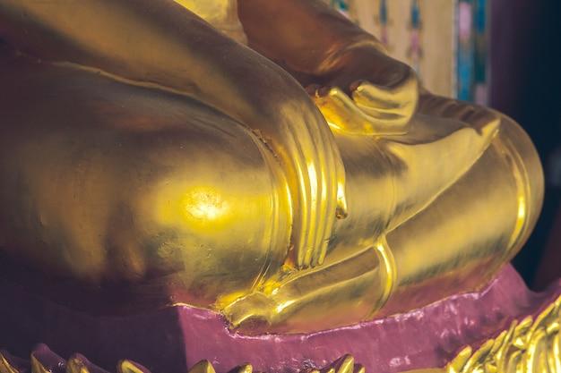 Statua dorata del buddha sul piedistallo con vecchie pareti
