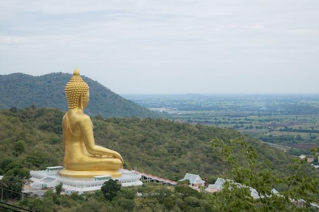 Statua dorata del buddha sulla montagna con il cielo