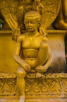 Statua dorata del ragazzo sulla fontana nel parco