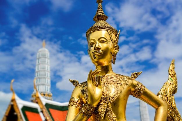 Statua dorata di kinnari al grande palazzo.