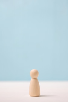 Statuetta di legno su sfondo blu. il concetto di solitudine.