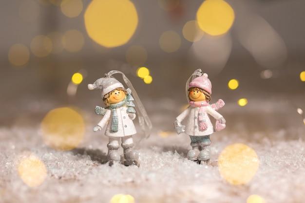 Statuette decorative a tema natalizio, statuetta ragazzo e ragazza in cappelli e sciarpe lavorati a maglia,