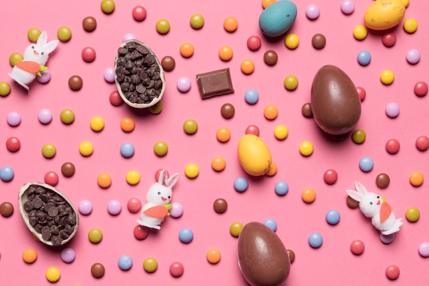 Statuette di conigli; uova di pasqua; gemme multicolori su sfondo rosa