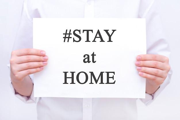 #stayathome. iscrizione resta a casa. su un pezzo di carta nelle mani di un uomo, un dottore. coronavirus, pandemia, resta a casa, resta al sicuro