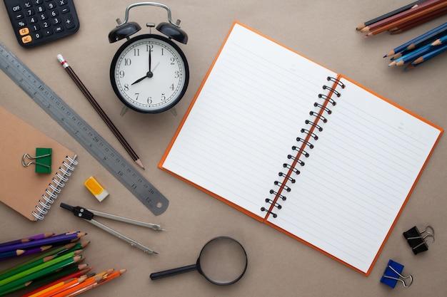 Stazionario con sveglia e taccuino di carta bianca, il piano creativo si distende dal concetto di scuola
