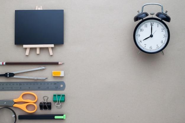 Stazionario con sveglia sulla scrivania dell'area di lavoro, flat lay di ritorno al concetto di scuola