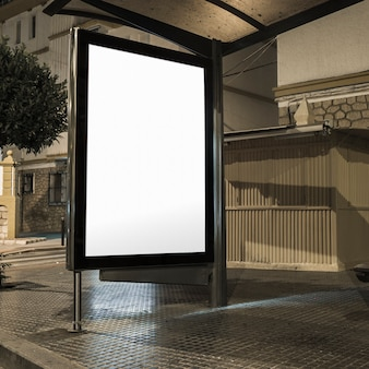 Stazione degli autobus con banner bianco illuminato su una strada