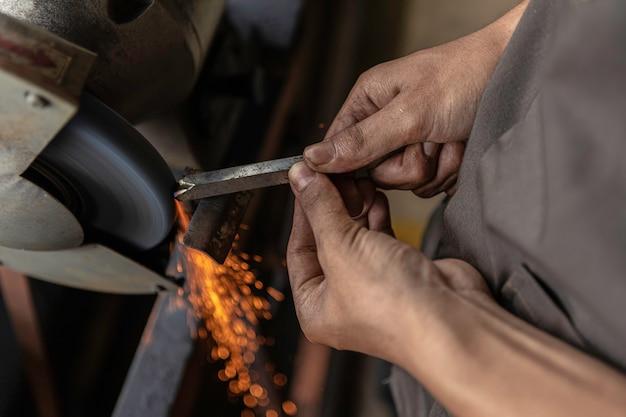 Steel grinder grinding steel per ottenere la nitidezza dell'acciaio. il fuoco è là fuori che ha premuto l'acciaio per macinare più velocemente.