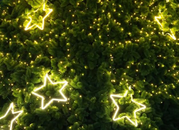 Stella d'oro su un albero di natale a sfondo notturno.