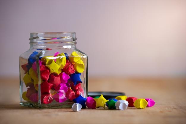 Stella di carta multicolore in bottiglia di vetro quadrato sul tavolo in legno con luce solare del mattino.