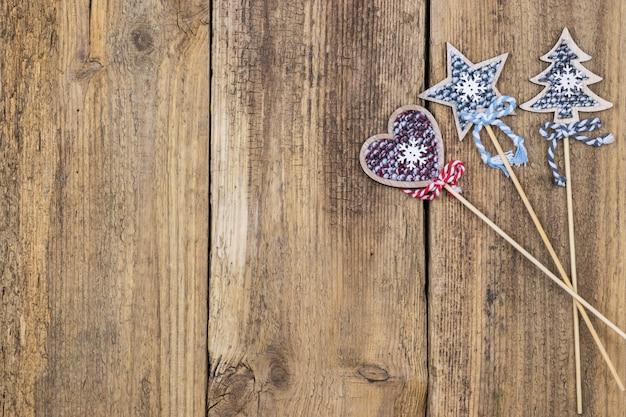 Stella di natale, albero di natale e cuore su uno sfondo di tavole di legno