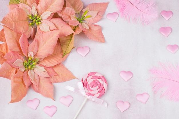 Stella di natale rosa, cuori di raso rosa, caramelle su un bastone e piume