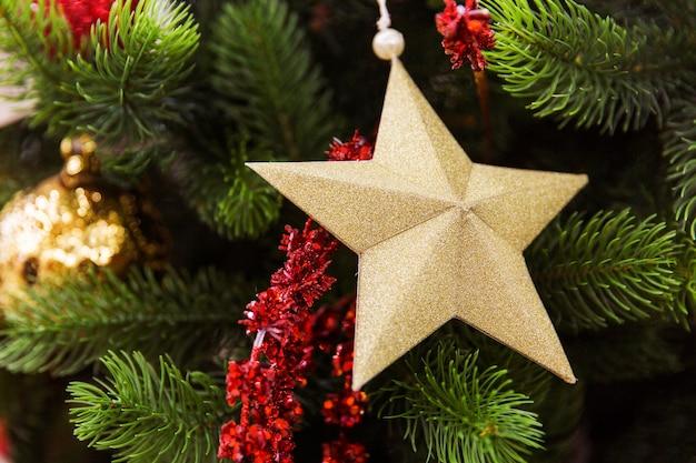 Stella dorata sul ramo di un albero di natale. giocattoli di capodanno. prepararsi per il nuovo anno
