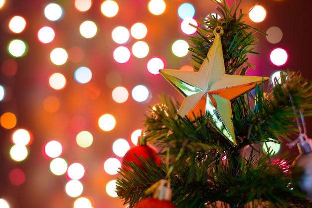 Stella e sfere della decorazione di natale che appendono sull'albero di natale dei rami del pino