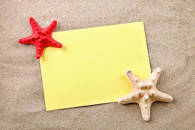 Stella marina, ciottoli e conchiglie sdraiati sulla sabbia sulla cartolina.