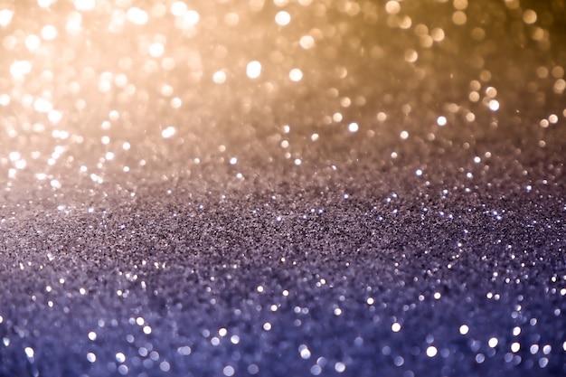 Stelle brillanti leggere blu e gialle dell'estratto di struttura del fondo del bokeh di natale su bokeh. sfondo di luci vintage glitter