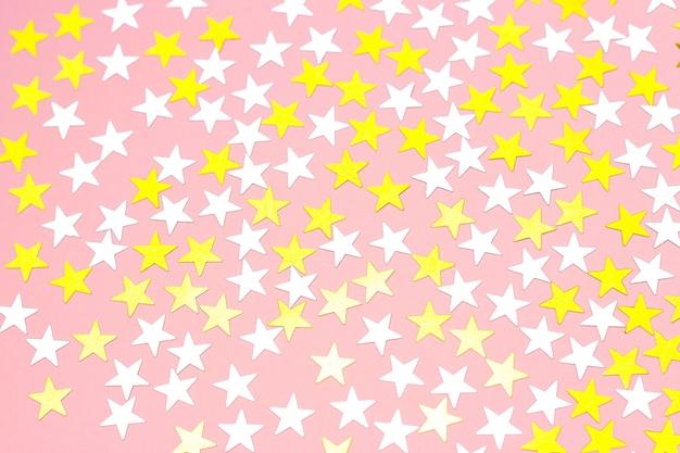 Stelle dorate di coriandoli su uno sfondo bianco, vista dall'alto