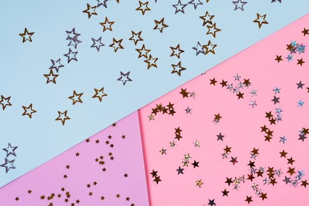 Stelle dorate di dimensioni diverse su sfondo blu rosa. tema di compleanno o festa. concetto minimale. disteso. vista dall'alto.