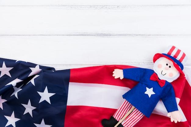 Stelle e strisce della bandiera americana e bambola blu-rossa su superficie bianca