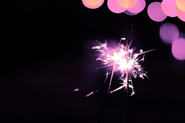 Stelle filanti luminose di festa su fondo nero. concetto di natale, vacanze ed eva, copia spazio