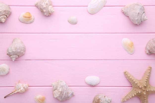Stelle marine e conchiglie su legno rosa. concetto di estate