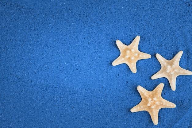 Stelle marine sullo spazio blu della copia della sabbia. sabbia colorata.