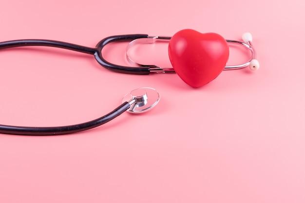 Stetoscopio a forma di cuore rosso su rosa. assistenza sanitaria, assicurazione sulla vita, giornata mondiale del cuore e concetto di cancro