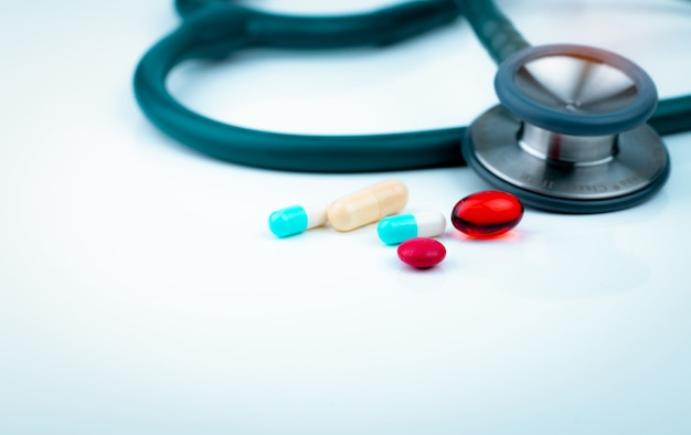 Stetoscopio con capsula bianco-blu, capsule di gel rosse morbide e compresse rotonde rosse sul tavolo del medico o sulla scrivania dell'infermiere.