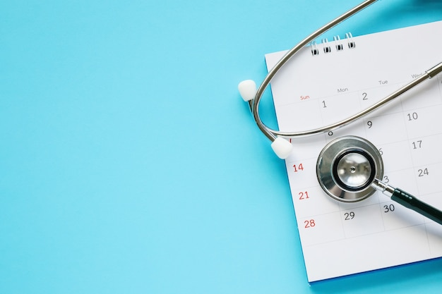 Stetoscopio con data di pagina del calendario su sfondo blu medico appuntamento medico concetto
