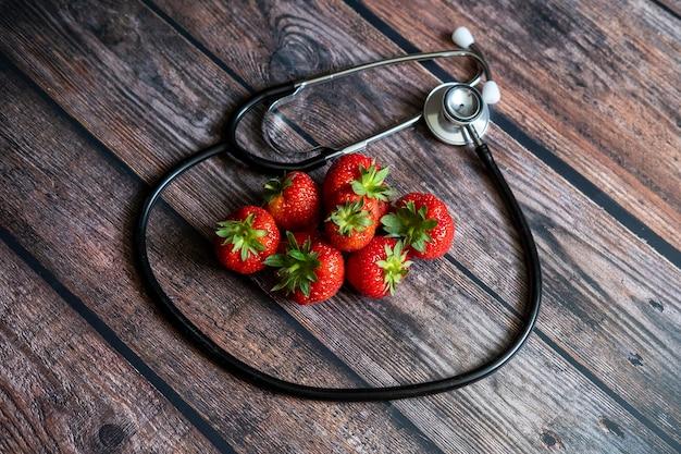 Stetoscopio con fragole in cima a un tavolo di legno. concettuale medico e sanitario.