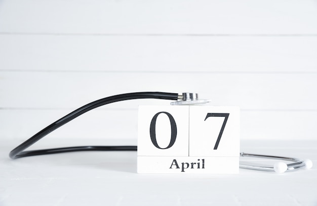 Stetoscopio con il calendario del blocco di legno del testo del 7 aprile su fondo di legno bianco.
