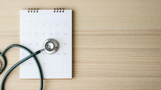 Stetoscopio con la data della pagina del calendario sul concetto medico di appuntamento medico del fondo della tavola di legno