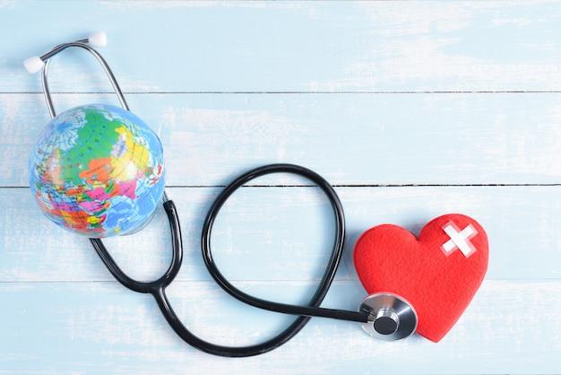 Stetoscopio, cuore rosso e globo su fondo di legno pastello blu e bianco.