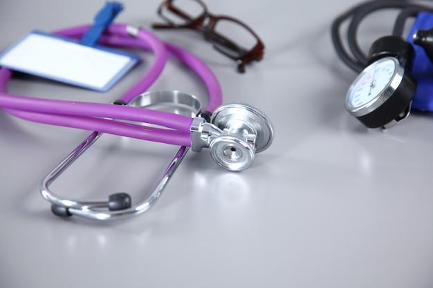 Stetoscopio, cuore rosso, occhiali e misuratore di pressione sanguigna su sfondo bianco. messa a fuoco selettiva.