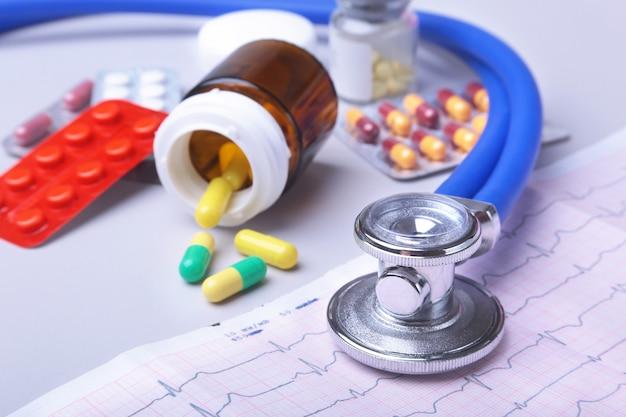 Stetoscopio del primo piano che si trova sulla prescrizione di rx con le pillole assortite. vita sana o concetto di assicurazione.