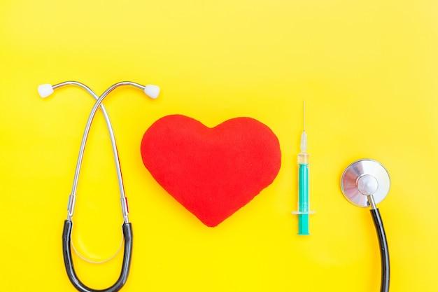 Stetoscopio dell'attrezzatura della medicina o siringa del phonendoscope e cuore rosso isolati su superficie gialla d'avanguardia