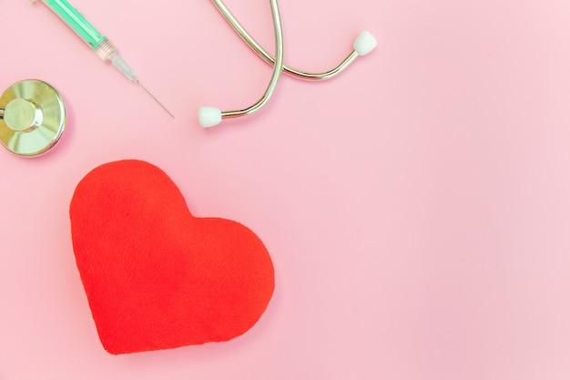 Stetoscopio dell'attrezzatura della medicina o siringa del phonendoscope e cuore rosso isolati sul fondo d'avanguardia di rosa pastello